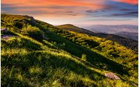 mountain ridge with peak behind the hillside. beautiful summer background at sunset with red sky