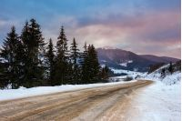 Empty asphalt mountain road under the snow  near the coniferous forest with cloudy sky in winter evening light