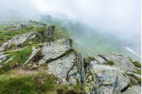 on the edge of rocky cliff of Fagaras ridge. mysterious scenery of Romanian highlands in thick fog. beautiful summer landscape. popular travel destination. couple of tourists in the distance