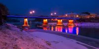 panorama of bridge through the river Uzh at night. beautiful cityscape of old european town Uzhgorod in winter