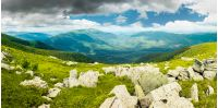 panorama of mountain landscape in summer. rocks lay among on a grassy slope down to the valley. beautiful view. overcast cloudy sky. windy summer weather.