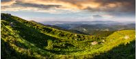 panorama of mountain ridge with peak behind the hillside. beautiful summer background at sunset with cloudy sky