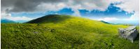 panorama with rock on the grassy hill in mountains. beautiful summer landscape. idyllic nature scenery. blue sky surrounded with clouds