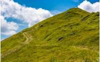 path uphill to the peak of mountain ridge. gorgeous summer nature scenery with cloudy sky. beautiful tourism background