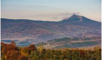 ridge with high peak above hills with forest. lovely mountainous background in late autumn