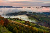 rising cloud covers rural fields in mountains. spectacular autumnal countryside scenery with mountain ridge in a distance at dawn