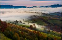 rising fog covers rural fields in mountains. spectacular autumnal countryside scenery with mountain ridge in a distance at dawn