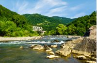 river in forested mountains. beautiful summer landscape with huge rocks on the shore and a white metal train bridge in the distance