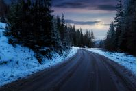 road through pine forest in mountains at night in full moon light. mysterious transportation winter scenery. path winding down the hill
