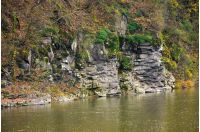 rocky cliff over the river in forest. beautiful autumn background with lots of textures