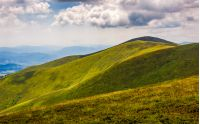 rolling hillsides of Carpathian mountain ridge. Beautiful nature background with cloudy sky