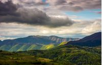 Rural area in mountains. Spectacular Carpathian mountain ridge in the distance on cloudy day