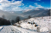 rural road in snowy mountainous area. beautiful winter scenery on a bright sunny day. mountains with snowy tops in a far distance