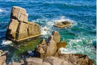 sea wave attacks the boulders of rocky shore and is broken about them