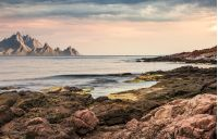seascape with rocky coast and mountain ridge with high peaks. composite landscape with cloudy sky at menacing sunrise