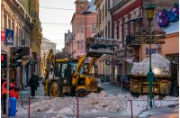 Uzhgorod, Ukraine - January 19, 2017: snow removal on streets of old town. people remove snow huge amount of snow with the help of shovels and tractor