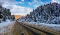 snowy road through mountains in evening. wonderful nature scenery in winter
