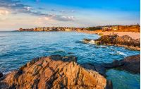 SOZOPOL, BULGARIA - SEPTEMBER 9, 2013: sunrise on sandy city beach in mellow season. Beautiful and warm weather on the shores of Black sea.