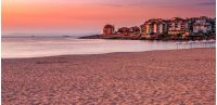 SOZOPOL, BULGARIA - SEPTEMBER 11, 2013: sunrise on sandy city beach in mellow season. Beautiful and warm weather on the shores of Black sea.