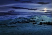 three hills in summer landscape at night in full moon light. beautiful countryside scenery.  tilt-shift and motion blur effect applied.
