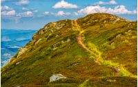 tourists footpath over the hill top. beautiful grassy mountain meadows with rocks on humps