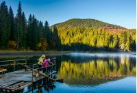National Park Synevyr, Ukraine - October 23, 2016: tourists on Synevyr lake feed fish from the raft. high altitude mountain lake among spruce forest on beautiful foggy morning