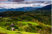 Countryside landscape in Carpathian mountains. village on grassy sunlit hills in the morning. dramatic sky over gorgeous mountain ridge in the distance