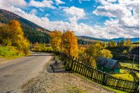 winding road through village in mountains. beautiful Carpathian rural scenery. gorgeous afternoon autumn weather with stunning sky