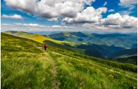 woman in red hikes through grassy slope in mountains. beautiful summer landscape in fine weather with few clouds on a blue sky