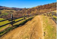 Spring time rural landscape. Wooden fence along the path through agricultural fields in Carpathian mountains