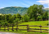 composite image of wooden fence on agricultural grassy meadow with trees on hillside in high mountains