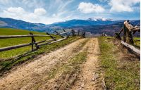 wooden fence on rural hill in spring. lovely mountainous landscape with snowy peaks in the distance