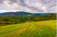 wooden fence on hillside with rural field in mountains. beautiful countryside landscape on cloudy day