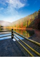 wooden pierce fence on a lake in fog. beautiful autumnal scenery in forest in mountains