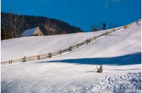 woodshed above the snowy hillside with wooden fence. lovely mountainous rural scenery