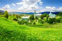 Composite image of green Monastery in mountains on hillside with grass and dandelions in morning light