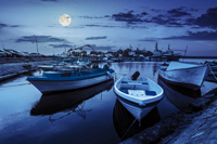 small fishing boats and few big one docked near embankment in port of Bulgarian town Sozopol at night in full moon light