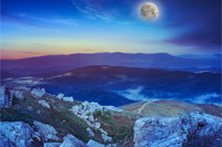 night mountain landscape with moon. valley with stones on the hillside. forest on the mountain under the beam of light falls on a clearing at the top of the hill.