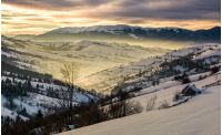 beautiful countryside in mountains at sunrise. village and rural fields on hillsides of valley covered with snow shine in morning light