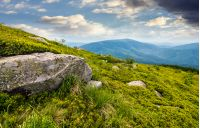 boulder on the grassy hillside. beautiful mountain landscape