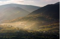 foggy autumn sunrise in mountainous rural area. village and forest with yellow trees on hills of beautiful mountain ridge