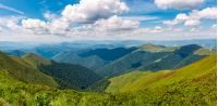 gorgeous panorama of mountains on fine summer day. fluffy clouds on a blue sky