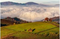 haystack on hillside above the clouds at sunrise. gorgeous rural landscape in high mountains