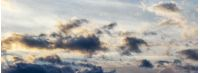 panorama of gorgeous cloudscape at sunset. beautiful nature background with golden fluffy clouds