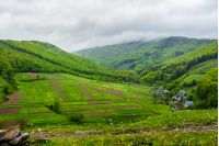 village in mountains behind the agricultural meadow with flowers on  hillside