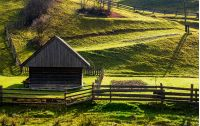 woodshed near the fence on grassy hillside. beautiful rural scenery in autumn